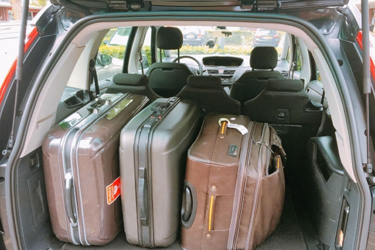 目下の者が荷物を預かりトランクに荷物を入れる